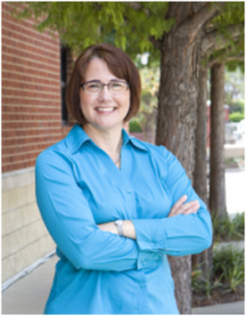 Image of Dr. Goldman standing outside wearing a turquoise blouse, arms crossed and smiling. She is wearing glasses and a watch. Red brick and off-white stone building and 3 trees are in the background.