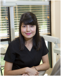 Image shows Noemi wearing black scrubs, facing the camera and sitting with wrists crossed on dental assistant's chair in dental operatory. She is smiling. There is a window behind her with blinds open and trees outside.